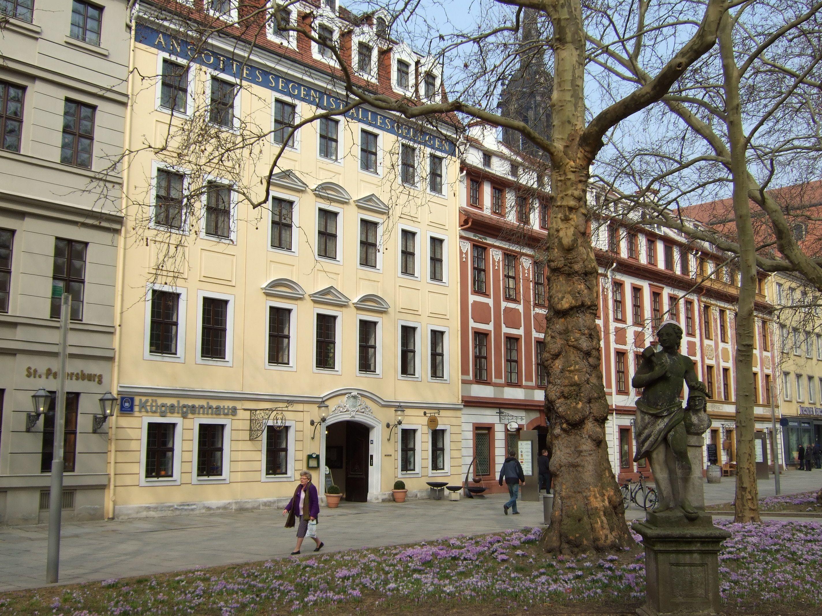 """Das Kügelgenhaus auf der Dresdner Hauptstraße. Das Haus hat 3 Etagen und zwei Dachgeschosse. An der Fassade steht in goldenen Buchstaben auf blauem Grund der Spruch: """"An Gottes Segen ist alles gelegen""""."""